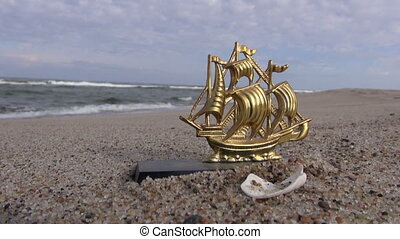 Golden ship statuette in the sand by the sea on overcast day...