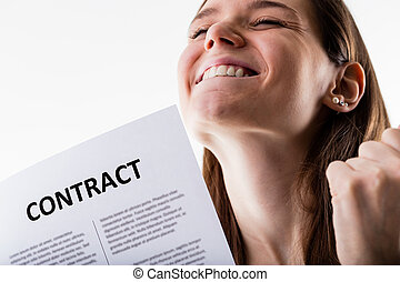smiling woman holding a contract and exulting because she's...