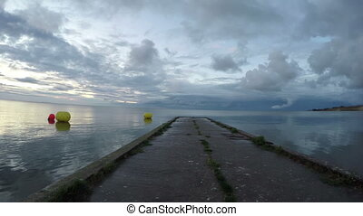 Cement pier in Curonian Lagoon with buoys on cloudy morning,...