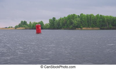Red buoy floating on fresh water river
