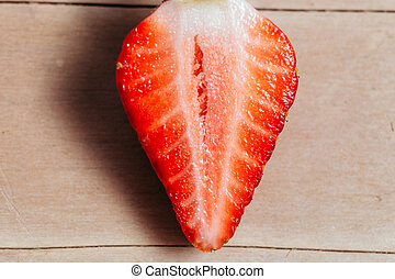 strawberry sliced macro on plate wood background top view