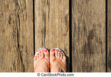 Female feet with flip-flops on wooden background, top view