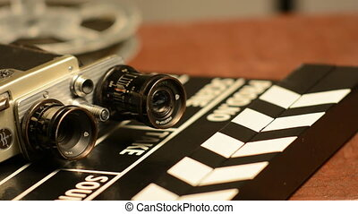 Movie clapper lie with retro camera and movie films on...