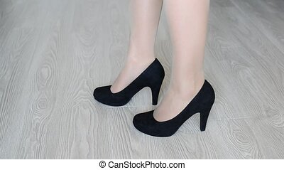 Woman takes off down a black high-heeled shoes - Woman takes...