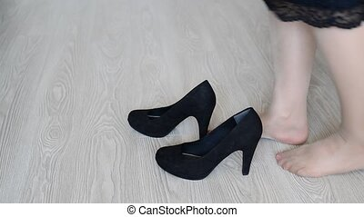 Woman puts on his feet black high-heeled shoes - Woman puts...