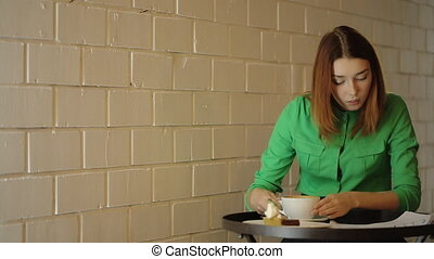 The young woman is checking the blueprints drinking coffee, working with architectural drawings