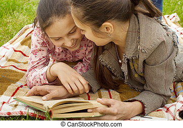two girls on the plaid reading book