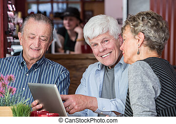 Three senior citizens using tablet computer in bistro -...