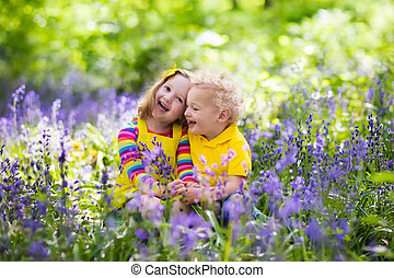 Kids playing in blooming garden with bluebell flowers - Kids...