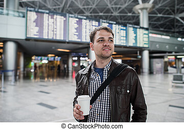 Young traveller man with coffee cup at the airport over board of departures and arrivals