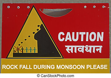 A notice board indicating Please Rock Fall During Monsoon, Caution, India