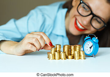 Smiling woman stacking gold coins into columns - Saving,...