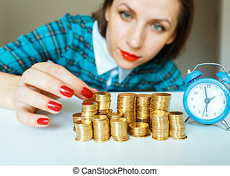 Woman stacking gold coins into columns - Saving, woman...