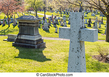 Many headstones in a cemetery with a cross in the foreground