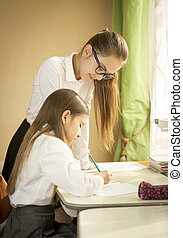 Elder girl helping with homework to younger sister -...