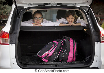 Two smiling schoolgirls looking through open car trunk -...