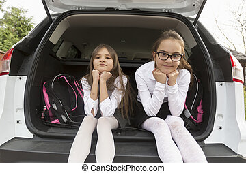Portrait of cute schoolgirls posing in open car trunk -...