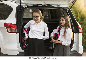 Portrait of two girls taking school bags out of car trunk -...