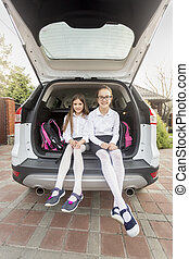 Two sisters ready to go to school sitting at car trunk - Two...