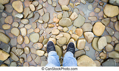 Toned shot of male feet in sneakers standing on pebbles in sea