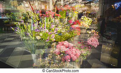 Toned shot of stands with flowers through store window -...