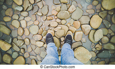Feet in sneakers standing on riverbank covered with pebbles