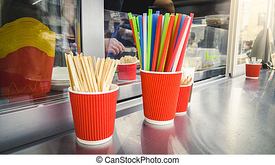 Closeup of cups, drinking straws and spoons on food truck...