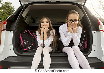 Portrait of two cute girls sitting in open car trunk - Funny...
