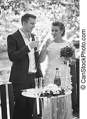 Black and white portrait of bride and groom drinking champagne at outdoor wedding ceremony