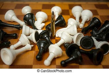 Conceptual photo of weapon power. Bullet among lying chess...