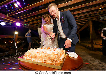 Happy bride and groom cutting wedding cake with knife -...
