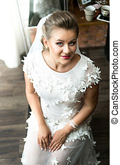Top view portrait of elegant smiling bride posing on chair...