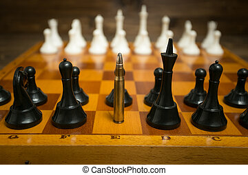 Riffle bullet in row of chess pieces. Concept of weapon...