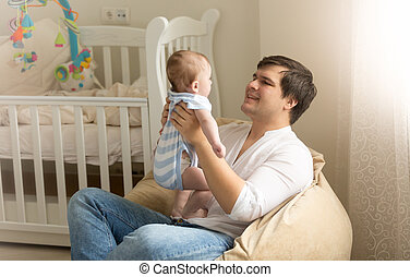 Portrait of young man playing with his baby at bedroom