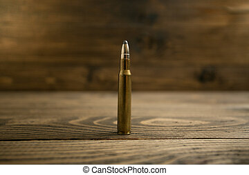 Closeup of riffle bullet on old wooden desk - Closeup photo...
