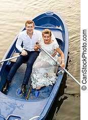 Newly married couple riding on rowing boat at evening -...