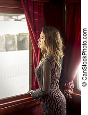 Rear view of sexy woman in dress looking out of train window...