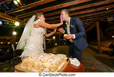 Funny portrait of bride feeding groom with wedding cake at...