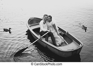 Black and white photo of bride and groom posing on old...