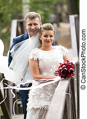 Happy bride and groom on wooden bridge at windy day -...