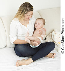 Beautiful mother sitting on bed with her cute baby boy -...
