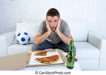 soccer fan in stress watching football game on television in sofa couch with pizza box and beer bottle