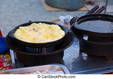 Fried mussel pancakes in big iron frying pan Tasty fried...