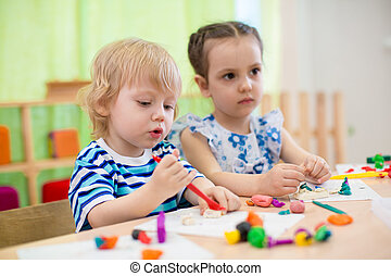 Kids doing arts and crafts Children in kindergarten - two...