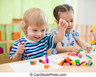 Happy children doing arts and crafts. Kids in kindergarten....