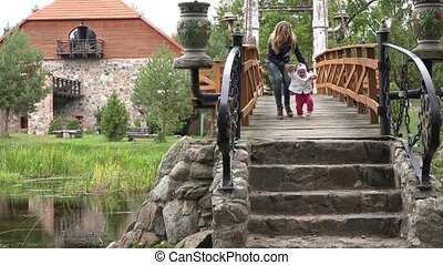 mother walk with baby girl on wooden bridge in park autumn....