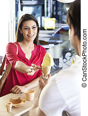 Mid Adult Woman Receiving Ice Cream From Seller - Smiling...