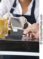 Saleswoman Accepting Payment From Customer In Cheese Shop