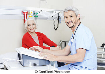 Physiotherapist Using Electromagnetic Machine - Portrait of...