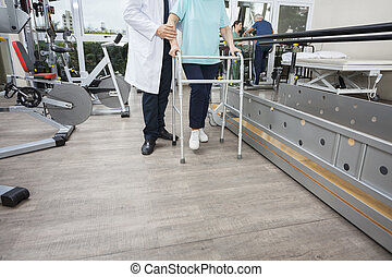 Low Section Of Physiotherapist Assisting Woman With Walker -...